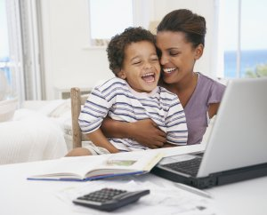 Mother and son at laptop laughing