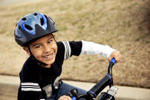 boy with helmet riding bike