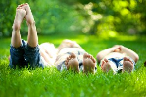 kids lying on grass in sunshine