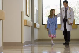 Doctor walking with patient in hospital corridor, girl (10-12) wearing dressing gown, smiling